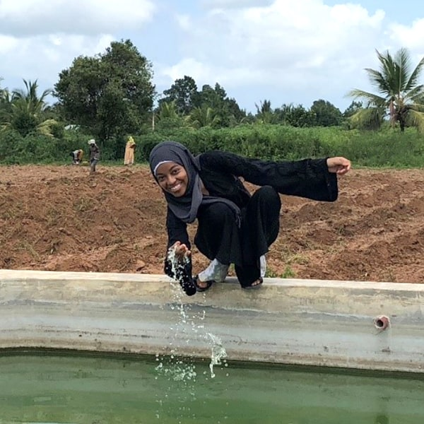 A young woman dipping her hand in a small pond on her farm