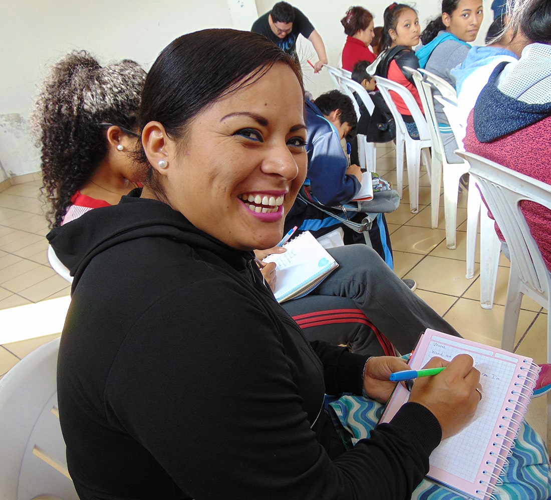 A woman smiling at the camera, writing in a notebook