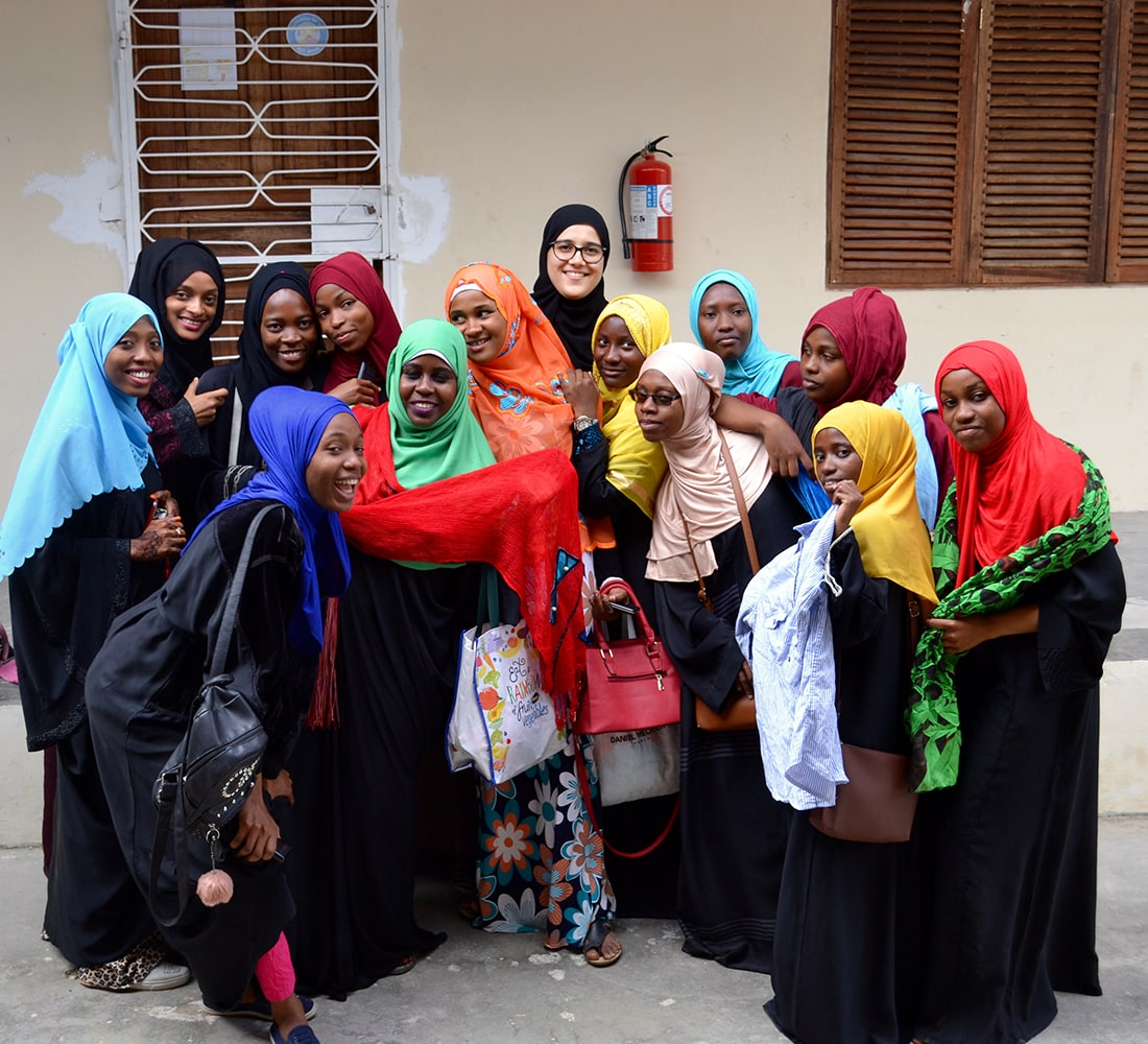 A group of 14 young women wearing colourful headscarves and smiling in Tanzania