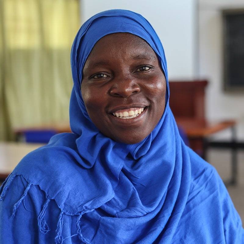 A woman with a bright blue headscarf smiling and looking at the camera while in a classroom
