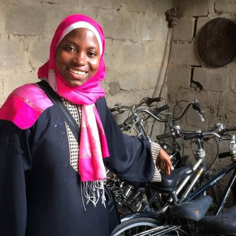 A young woman entrepreneur standing in front of a collection of bicycles