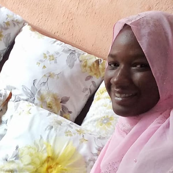 A young woman in a light pink headscarf standing in front of some pillows she made
