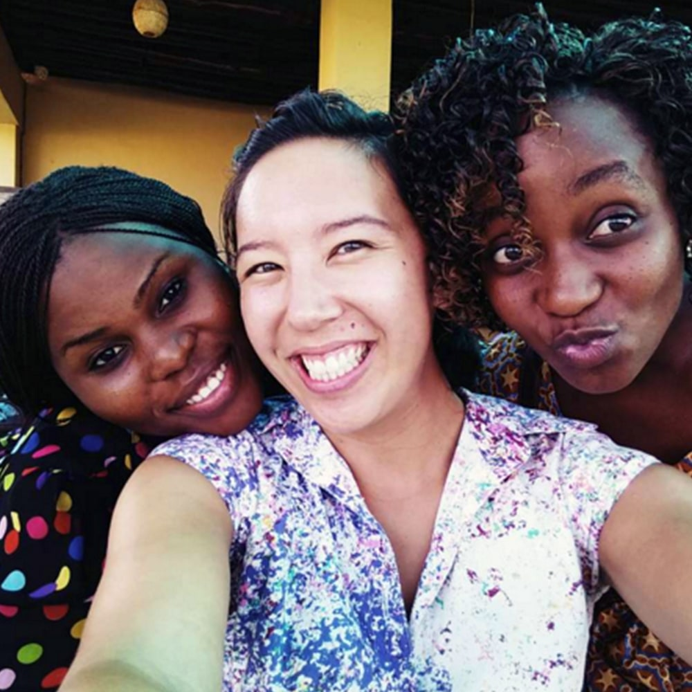A Canadian volunteer taking a selfie with two young women, all with big smiles on their faces in Tanzania
