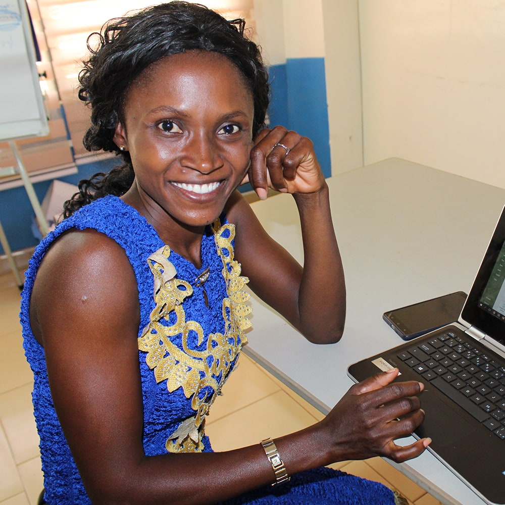 A young woman wearing a blue and gold dress, smiling at the camera while working on a laptop