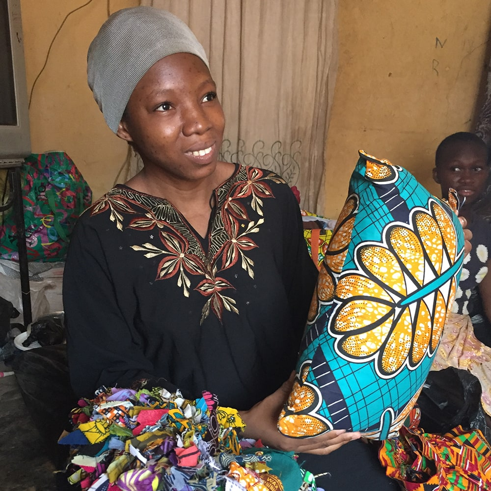 A young woman selling colourful pillows she made
